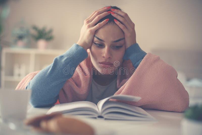 疲乏的学生女孩坐地板和阅读书 免版税库存照片
