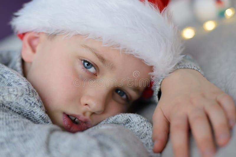 疲乏的孩子在床上的圣诞老人帽子在圣诞节 图库摄影