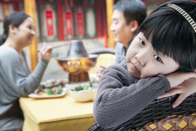 疲乏的小女孩画象家庭膳食的 免版税库存图片