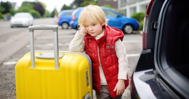 疲乏的小男孩准备好去与他的父母的旅行 库存照片