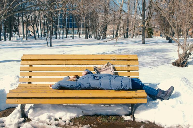 疲乏的少妇在一条长凳的公园睡觉在冬天 库存图片