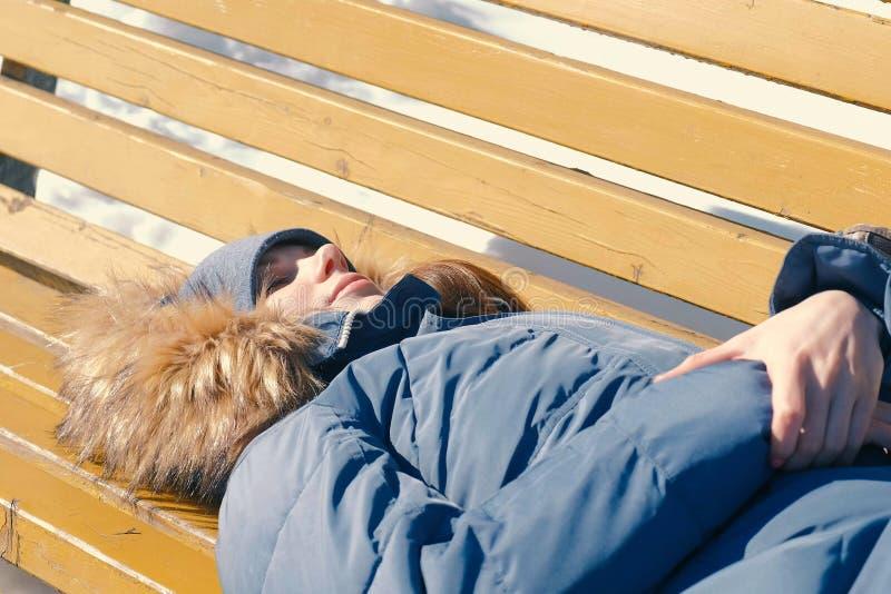 疲乏的少妇在一条长凳的公园睡觉在冬天 库存照片