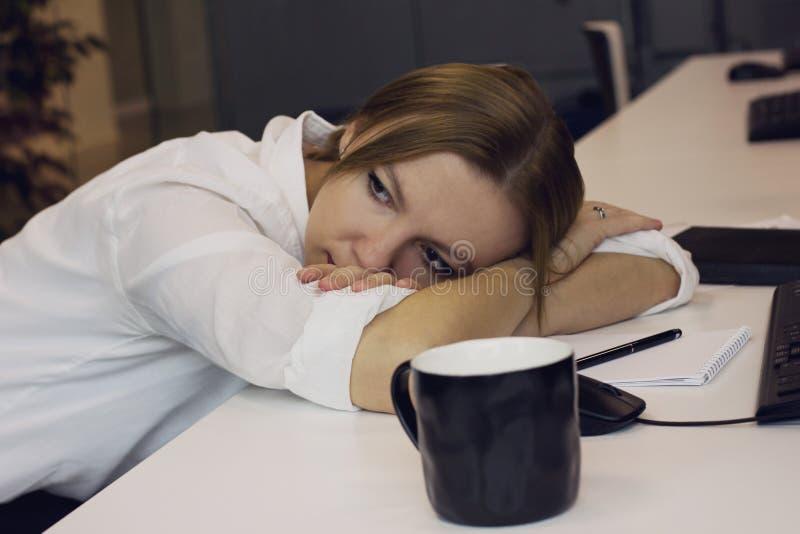 疲乏的少妇在书桌放置了她的头下来在办公室 免版税库存照片