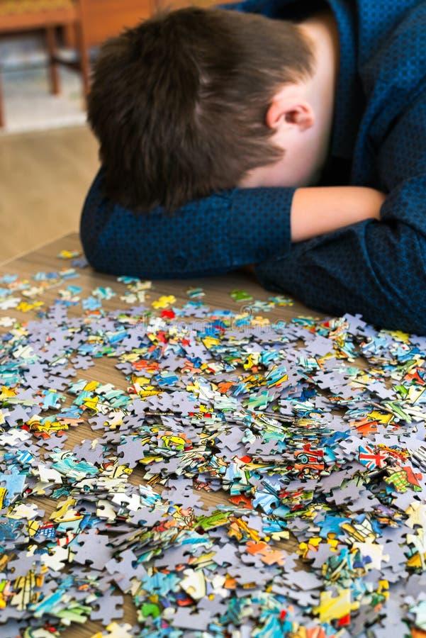 疲乏的少年坐掀动他的头在难题旁边 图库摄影