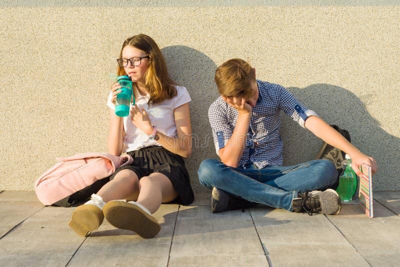 疲乏的少年学童在学校的灰色墙壁附近坐 库存照片