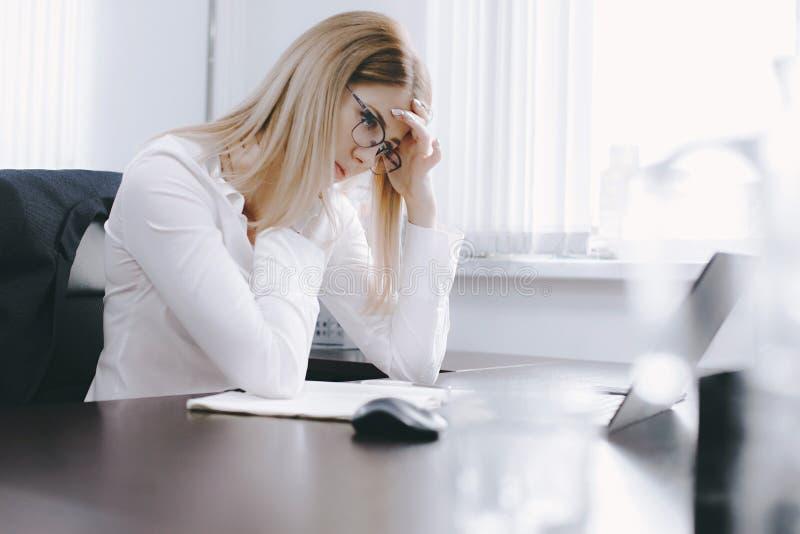 疲乏的年轻可爱的金发碧眼的女人,当工作在桌上在办公室时 库存照片