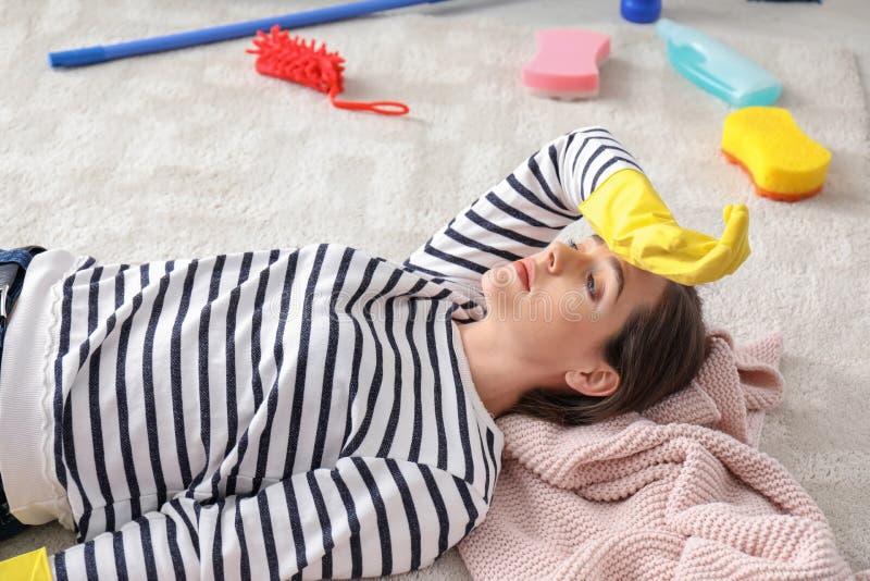 疲乏的年轻女人在清洗她的公寓以后 库存照片