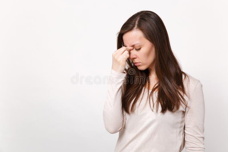 疲乏的年轻女人画象保留眼睛的轻的衣裳的关闭了,把手放在白色墙壁上隔绝的鼻子上 图库摄影
