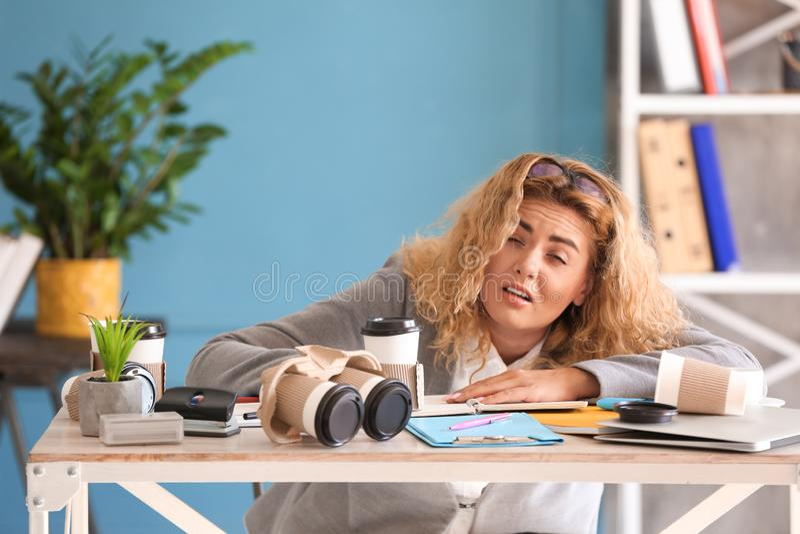 疲乏的年轻女实业家在桌上在办公室 库存照片