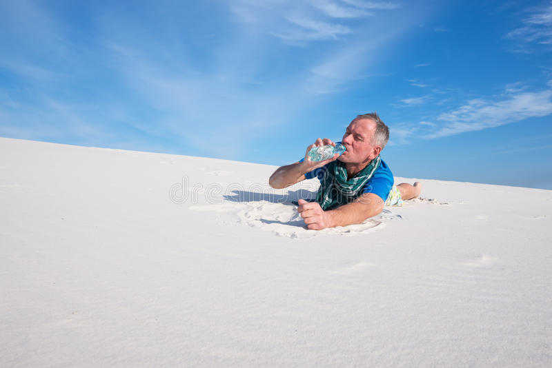 疲乏的旅客在渴在一个热的晴天的沙漠丢失了 免版税库存照片