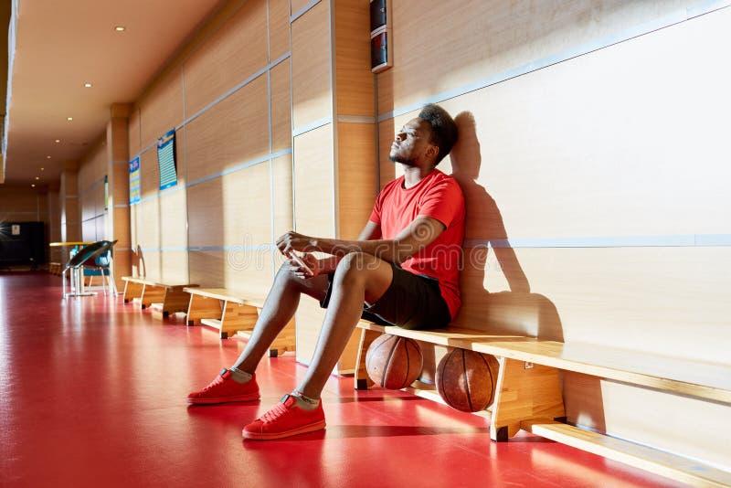 疲乏的美国黑人的蓝球运动员坐边线 图库摄影