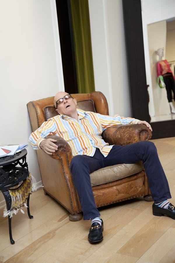 疲乏的老人坐在时尚精品店的扶手椅子 图库摄影