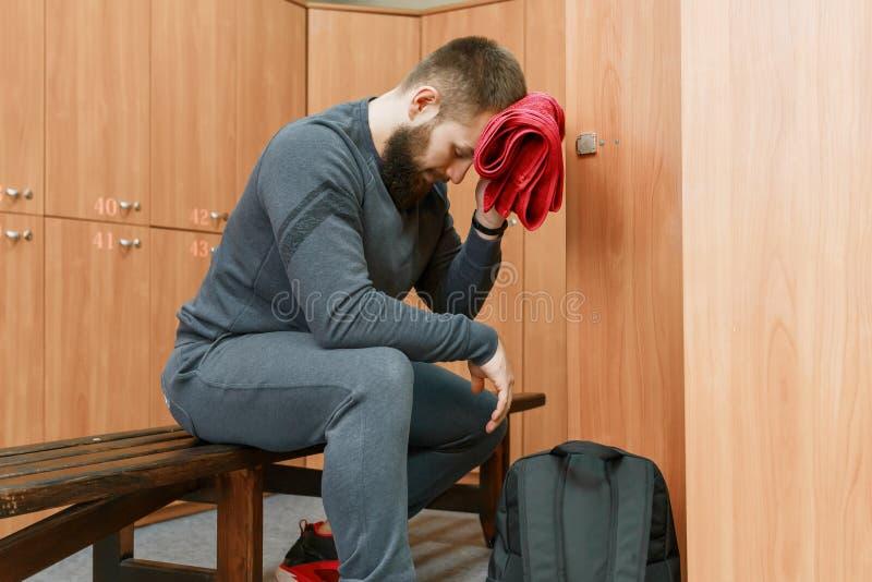 疲乏的肌肉有胡子的人在抹他的面孔的化装室与毛巾 免版税库存图片