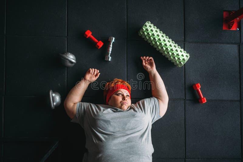 疲乏的肥胖妇女在健身房的地板上说谎 图库摄影