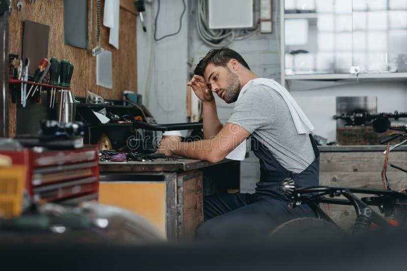 疲乏的英俊的专业安装工工作 免版税库存照片