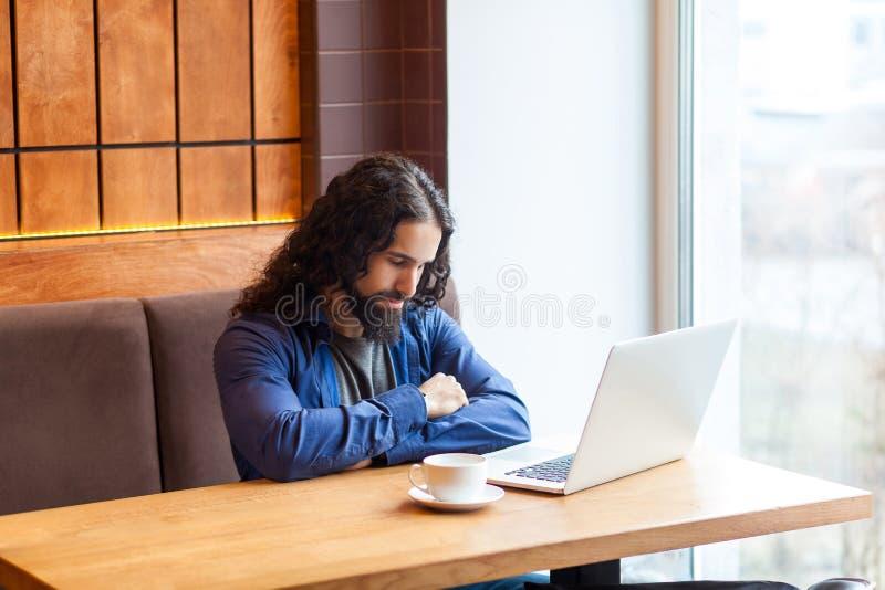 疲乏的英俊的年轻成人人自由职业者画象坐在与膝上型计算机的咖啡馆的便装样式的,睡觉在坚硬额外时间以后 免版税库存照片