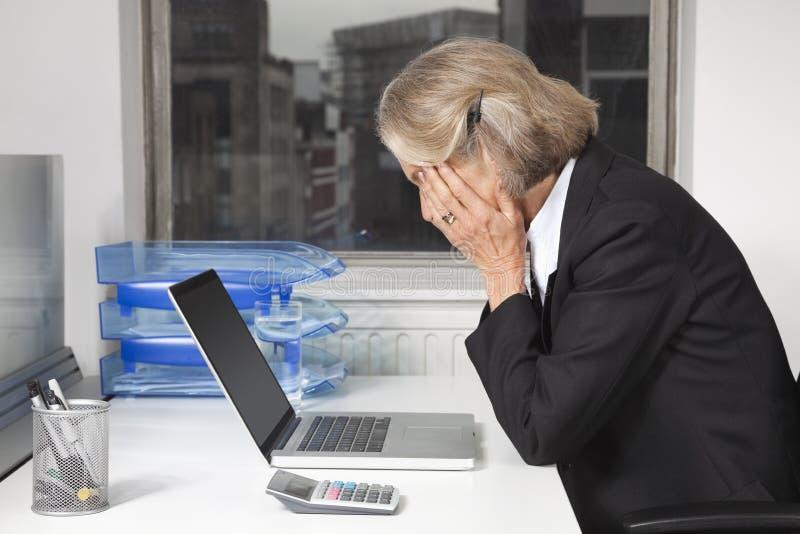 疲乏的资深女实业家侧视图在膝上型计算机前面的在书桌在办公室 库存图片