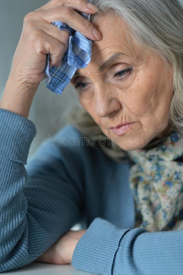 疲乏的资深妇女画象有手帕的 免版税库存图片