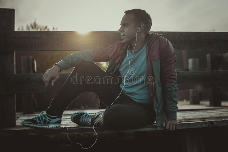 疲乏的赛跑者开会,放松和听在一个木码头的音乐电话,体育 免版税库存图片