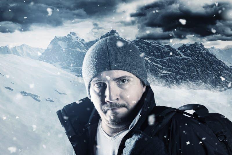 疲乏的远足者画象在山风景前面的在冬天 库存图片