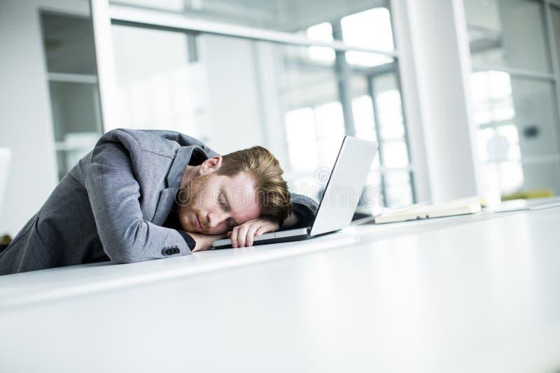 疲乏的年轻人在办公室 库存照片