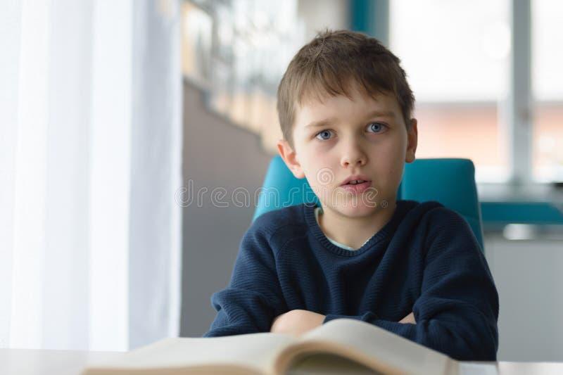 疲乏的8岁做他的家庭作业的男孩在桌上 免版税库存图片