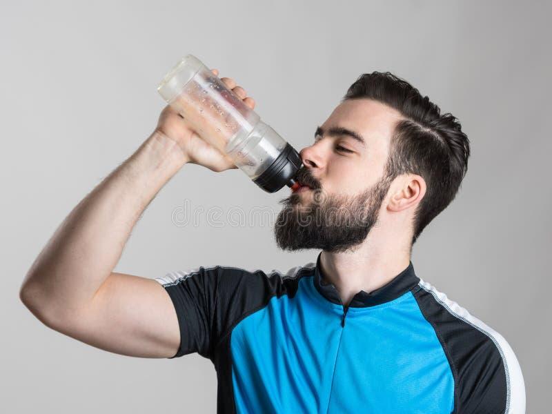 疲乏的从瓶容器的骑自行车者饮用水画象  库存图片