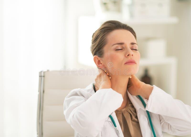 疲乏的医生妇女画象在办公室 免版税库存照片
