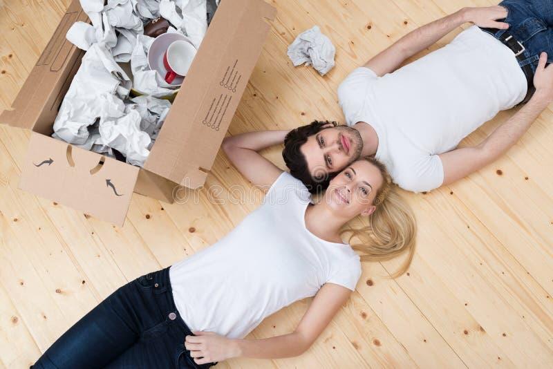 疲乏年轻夫妇说谎势均力敌在地板上 库存图片