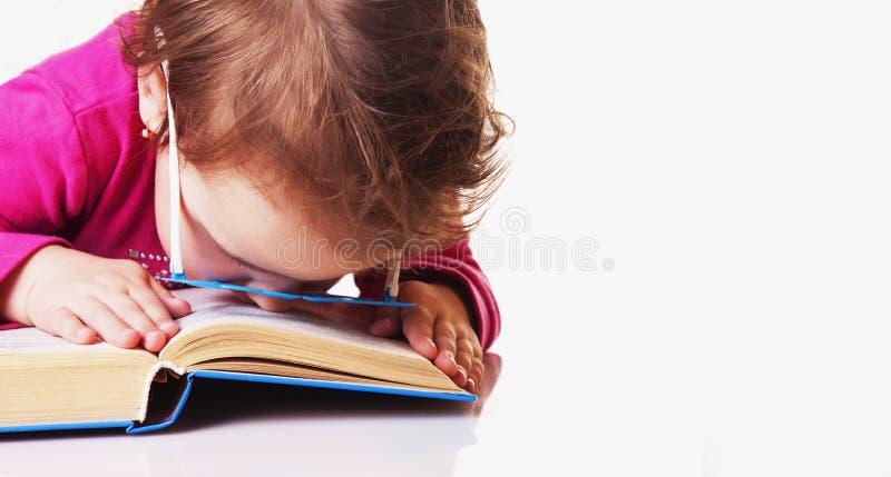 疲倦于读小女婴睡着了在书Knowled 库存照片