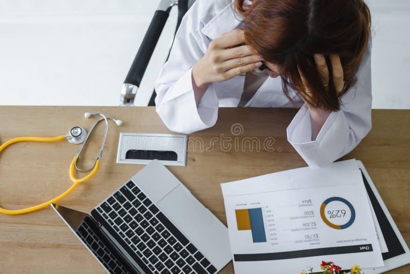 疲倦注重了年轻亚裔医生用在面孔的手遭受在工作场所的严重消沉 免版税库存图片