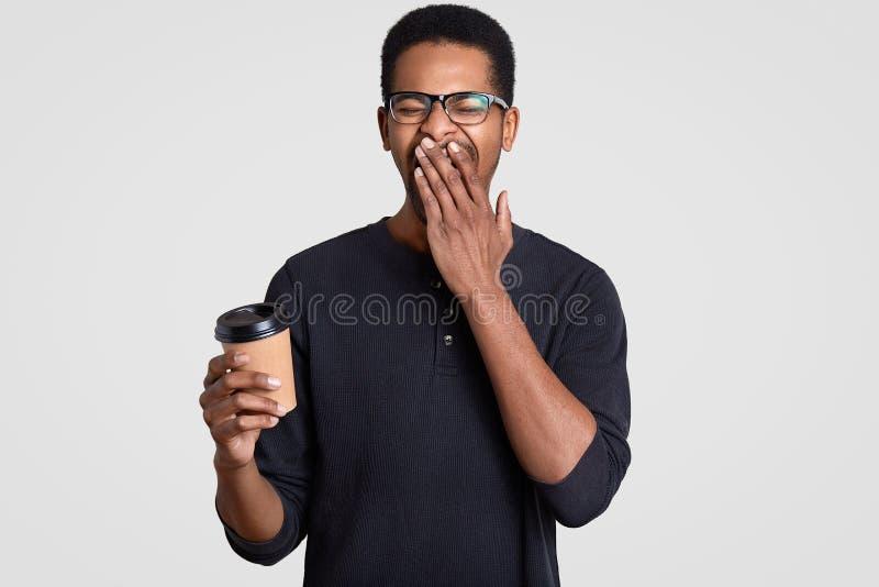 疲倦的劳累过度的年轻行家照片用棕榈盖嘴,感到困,拿着外带的咖啡,戴透明眼镜, 库存图片