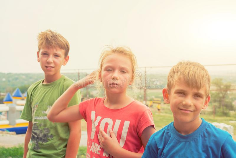 疲倦的孩子在步行、姐妹和两个兄弟以后的一个极端公园在坚硬竞争以后休息 免版税图库摄影