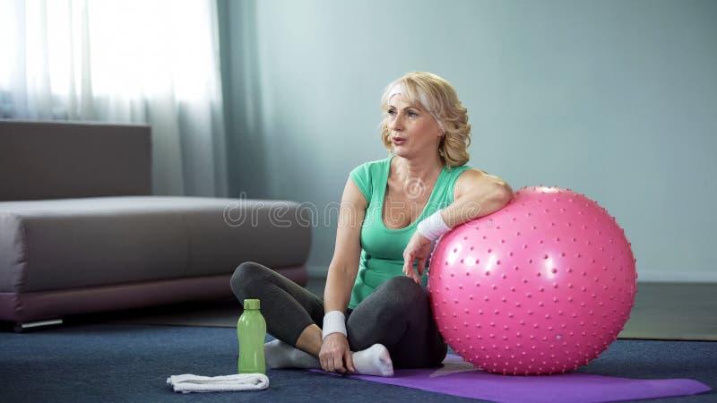 疲倦的成熟妇女坐休息在锻炼以后的席子,倾斜在fitball 免版税库存照片