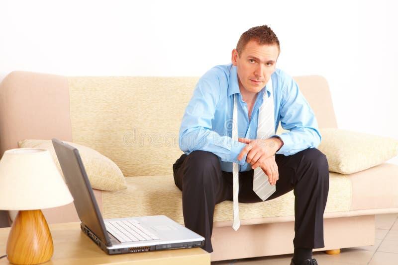 疲倦的生意人坐的沙发 库存照片