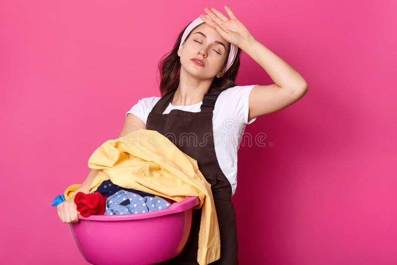 疲倦的繁忙的欧洲妇女拿着与肮脏的衣裳的水池,保持眼睛闭合,为洗涤做准备,佩带头饰带、围裙和t 免版税库存图片