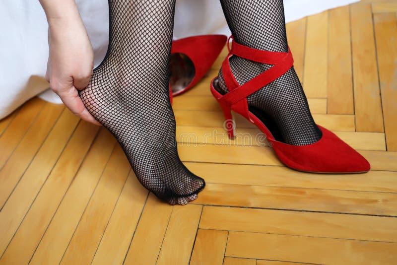 疲倦的腿,脚痛苦,离开在高跟鞋的妇女红色鞋子 库存图片