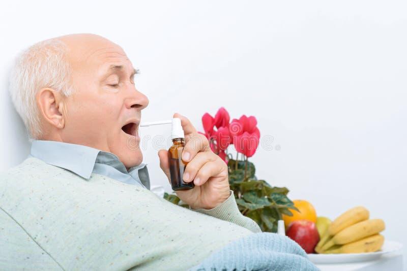 疲倦的资深绅士使用他的喉咙痛浪花 免版税库存照片