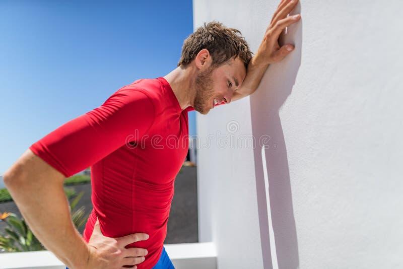 疲倦的运动员赛跑者人被用尽的倾斜在艰苦呼吸在困难的锻炼以后的疲劳墙壁 Fitnes人冒汗  库存图片