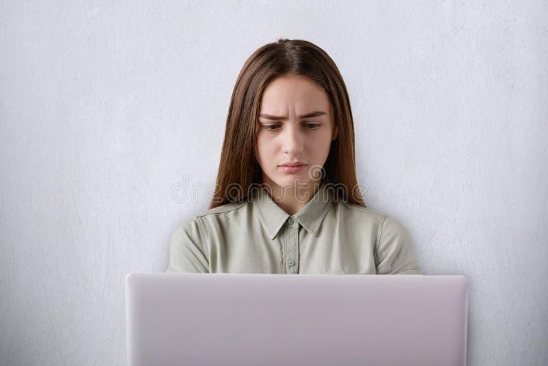 疲倦表示的生气的美丽的女孩画象与她的膝上型计算机一起使用被隔绝在灰色背景 学生h 免版税库存照片