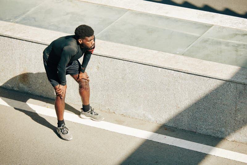 疲惫的运动员跪着 免版税图库摄影
