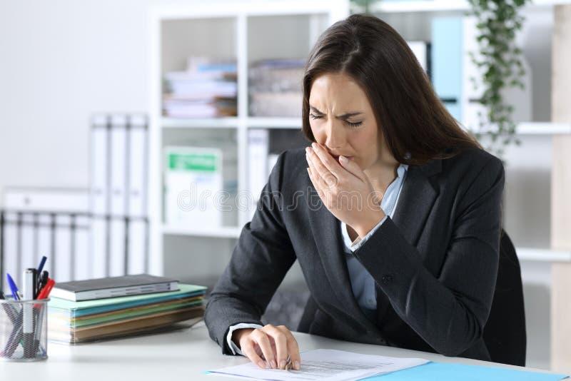 疲惫的高管妇女坐在办公桌上打哈欠 图库摄影
