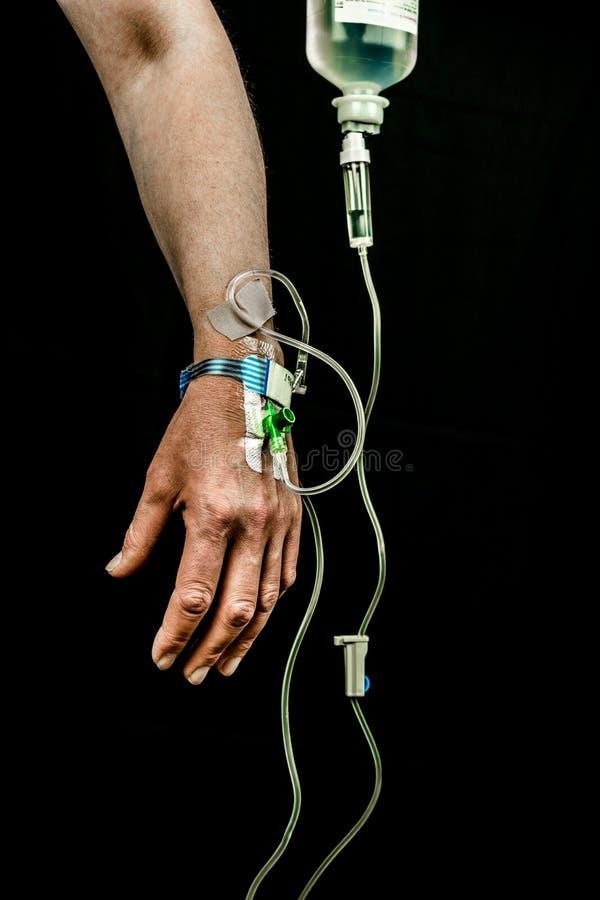 病人的手和胳膊有iv可变的治疗的在黑背景 库存图片