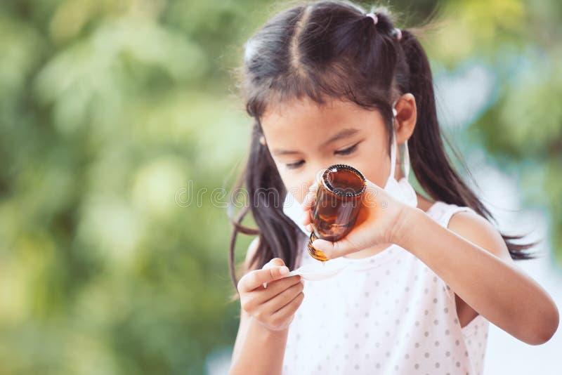 病态的亚洲女孩穿戴防毒面具采取糖浆医学 免版税库存图片