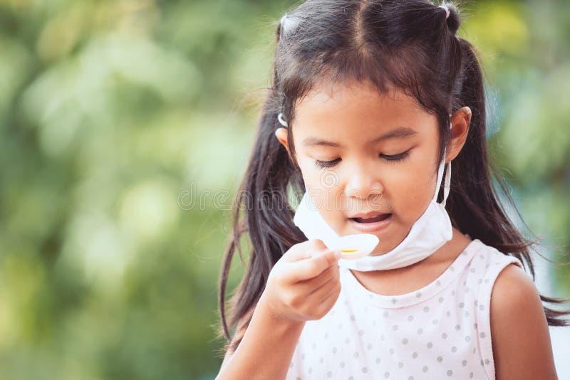 病态的亚洲女孩穿戴防毒面具采取糖浆医学 库存照片