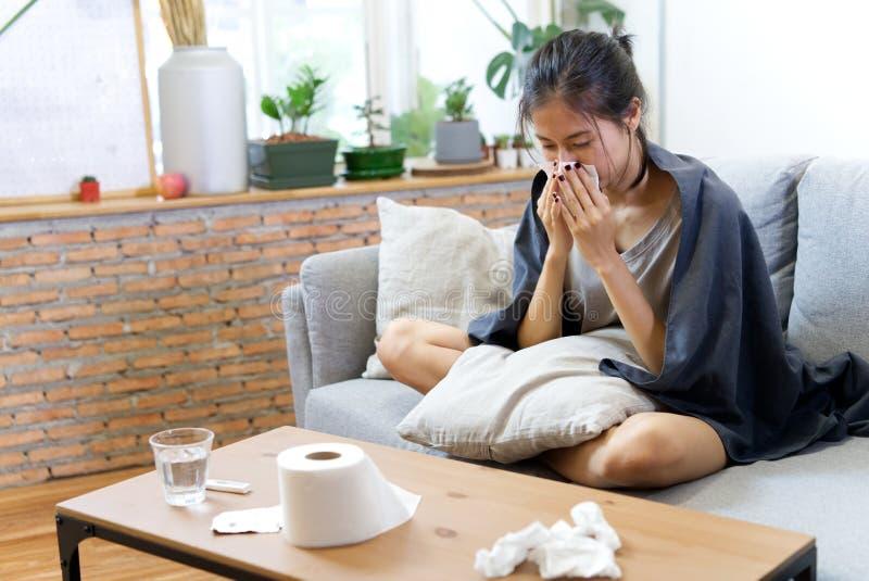 病态的亚洲年轻女人喷嚏在家在有寒冷的沙发 免版税库存图片