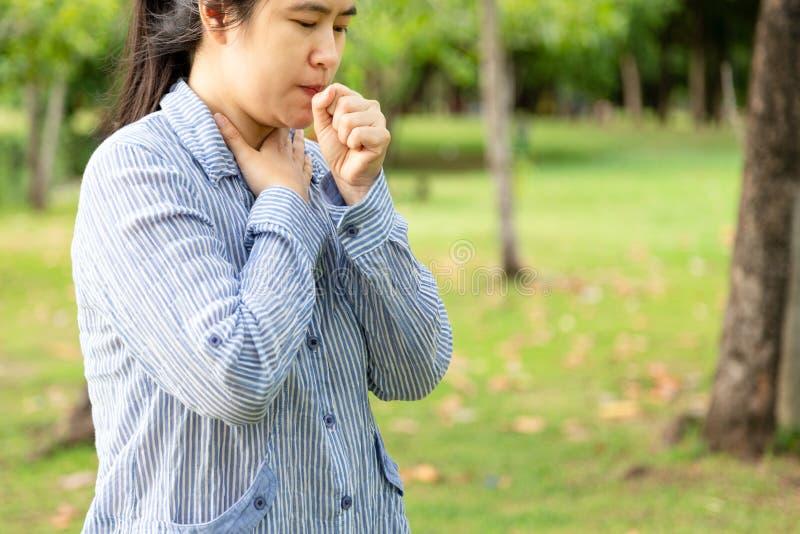 病态的从喉咙痛的妇女感觉坏痛苦,痛苦吞下,亚裔女性患者有咳嗽,激怒和喉咙痛 图库摄影