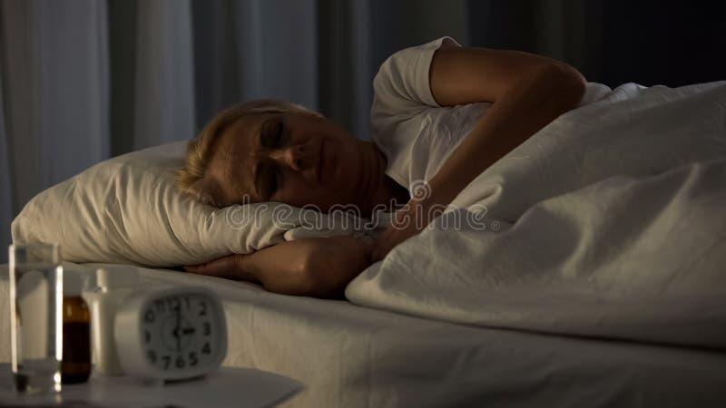 病态的年长女性睡觉医院病床夜,医疗保健,领抚恤金者招待所 库存照片