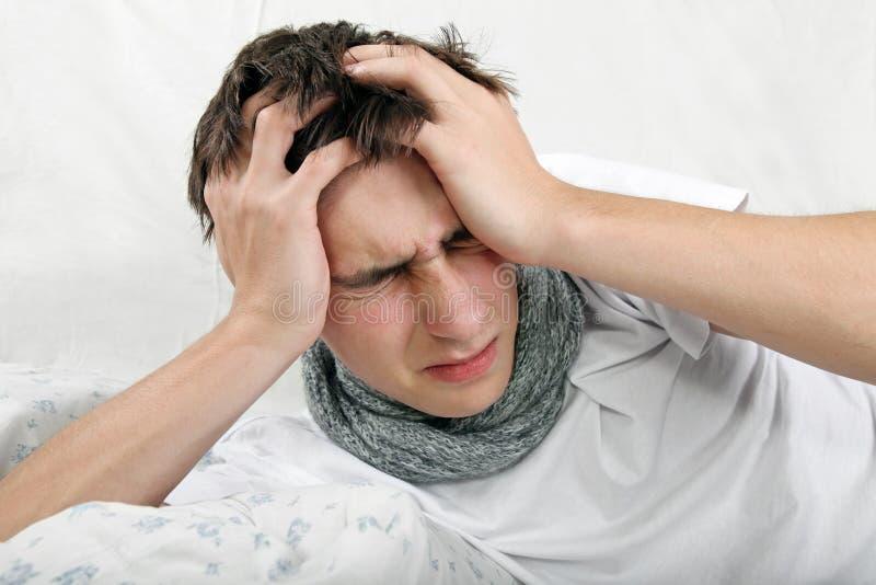病态的年轻人感受头疼 库存图片