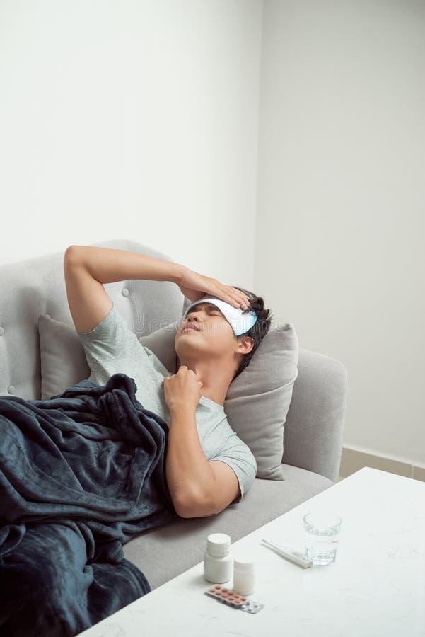 病残浪费了在沙发遭受的寒冷和冬天流感viru的人 库存照片